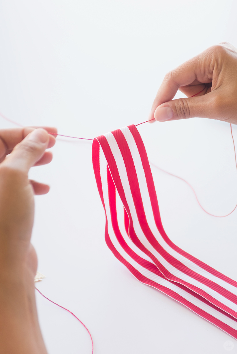 Tying a red and white ribbon to the July 4th Ribbon Garland.