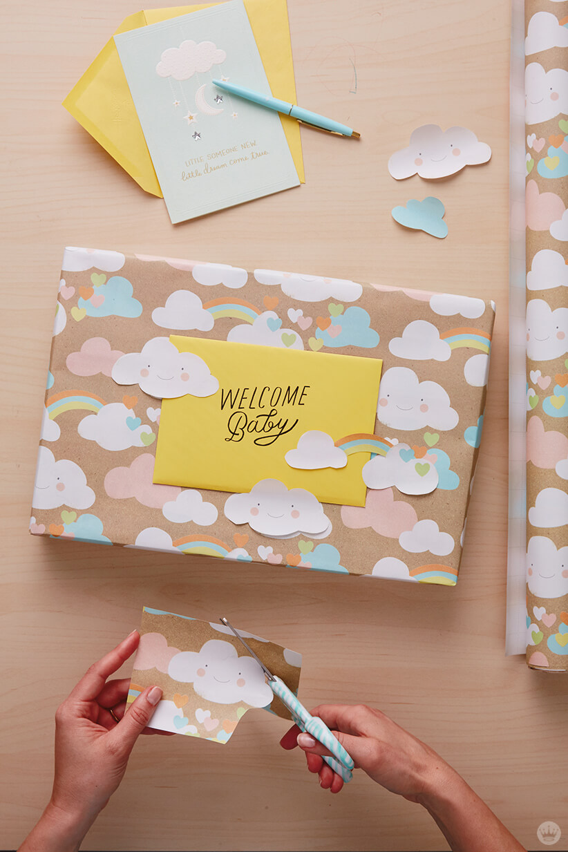 Dreamy baby gift wrap ideas: Use design cut-outs to hold the card in place
