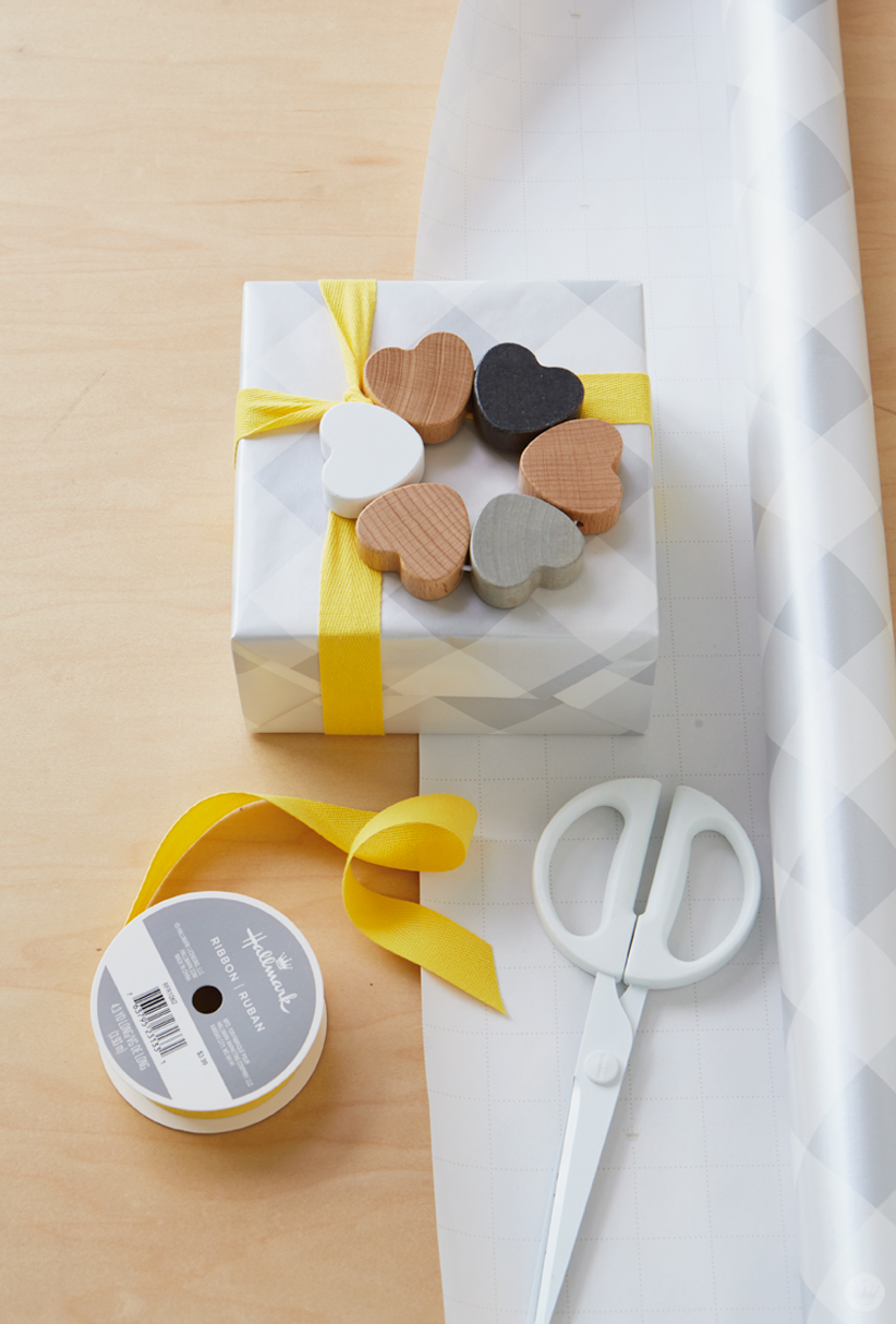 Box wrapped in large gray gingham print paper, wooden heart rattle tied on with yellow ribbon