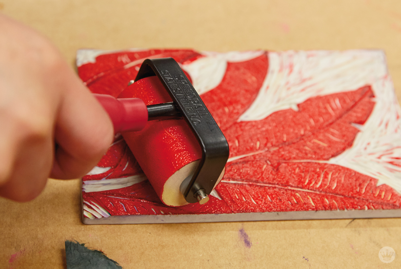 Adding ink to a linoleum stamp with a brayer