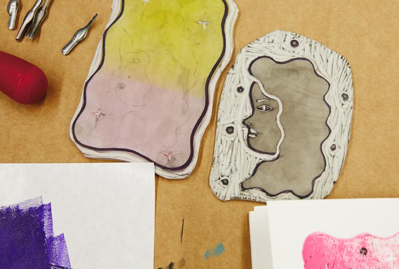 Hand-cut linoleum blocks used to create a layered illustration
