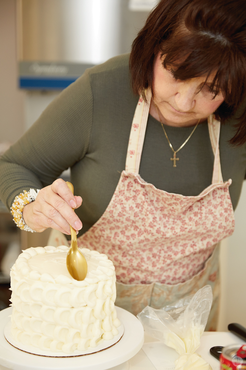Finishing the top of a petal cake by using a plastic spoon to flatten mounds of buttercream frosting