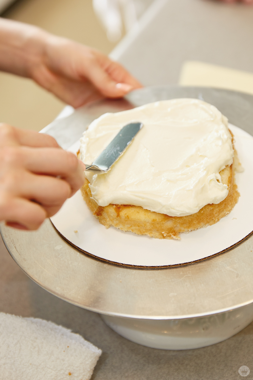 Spreading buttercream frosting over a layer of cake using an offset spatula