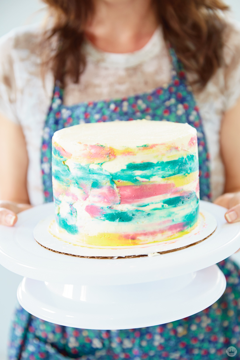 A layer cake decorated using pink, yellow, and green buttercream for a watercolor effect