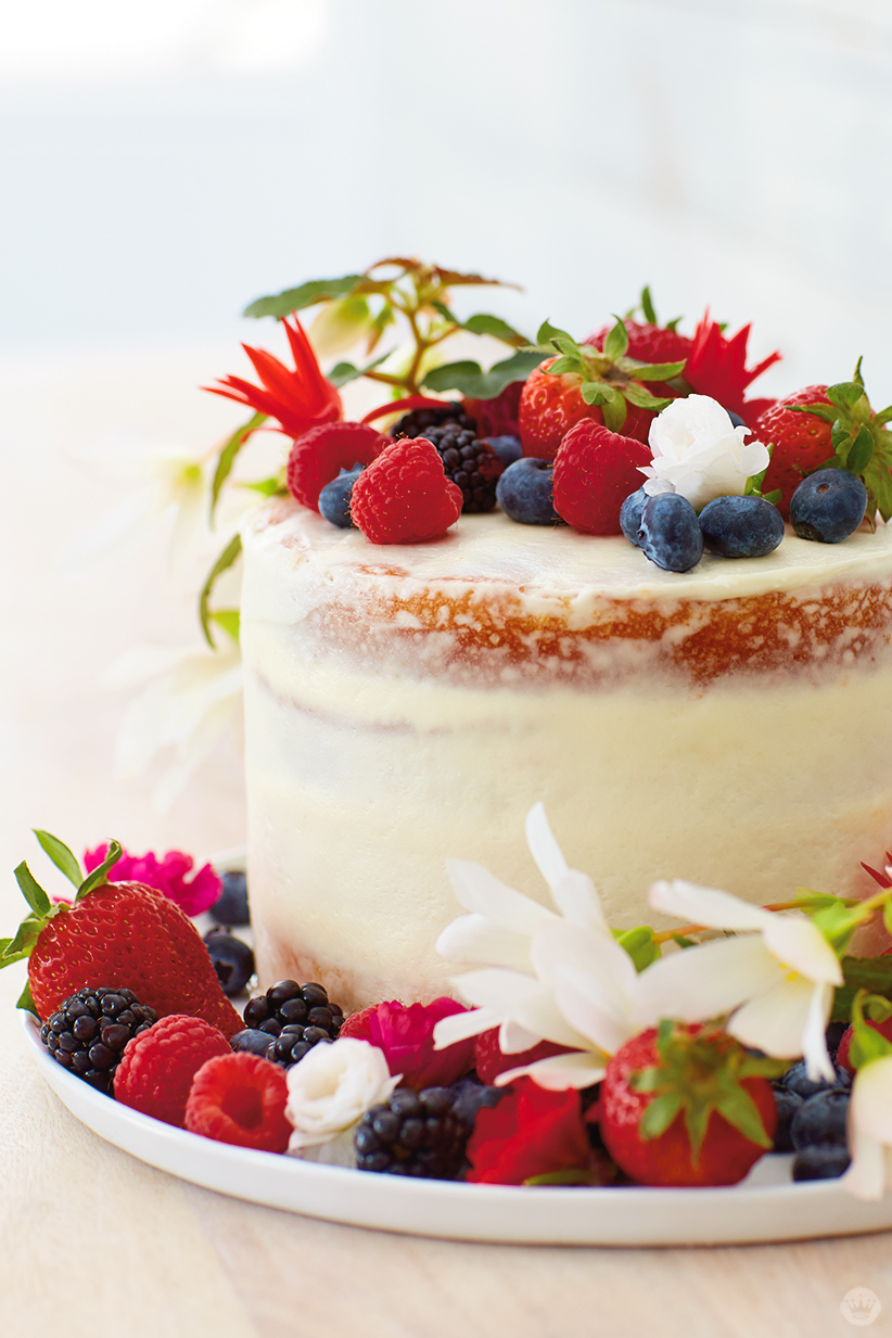 """Berries and flowers top a """"naked"""" cake"""