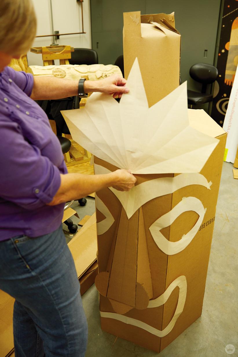 Hallmark artists explore cardboard Halloween costume ideas. Tiki sculpture in progress.