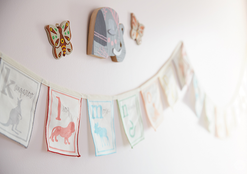 This children's room design features painted wooden cutouts of an elephant and butterflies, and an alphabet garland.