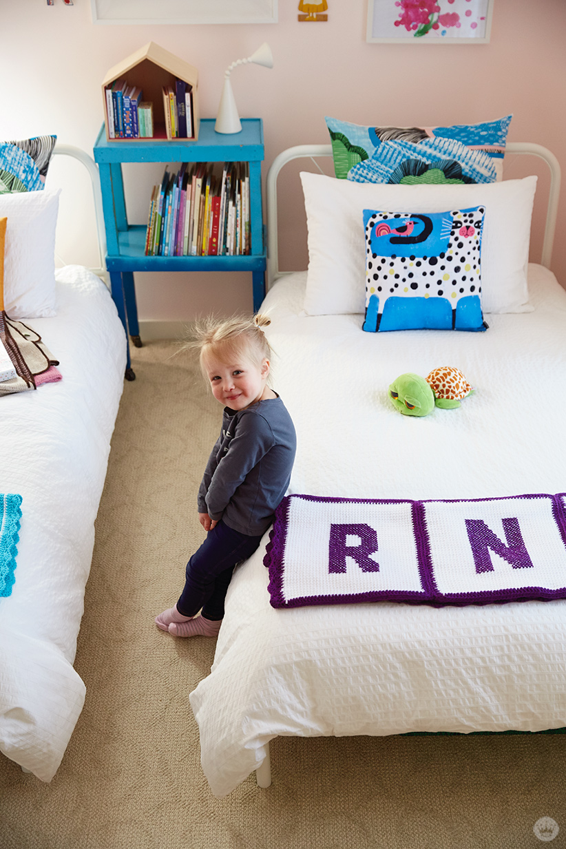 A toddler leans against a twin bed with a monogrammed afghan and colorful pillows.