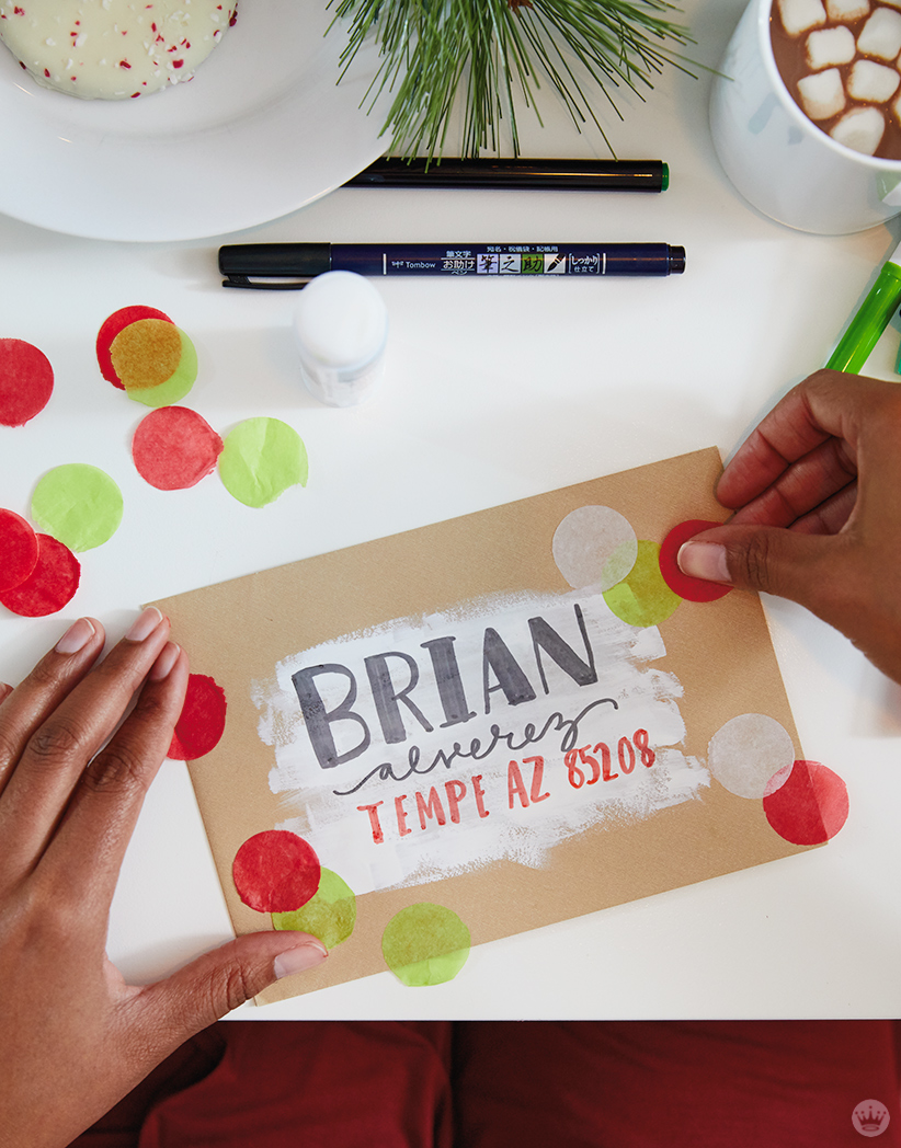 Decorating a holiday card envelope with tissue paper confetti circles