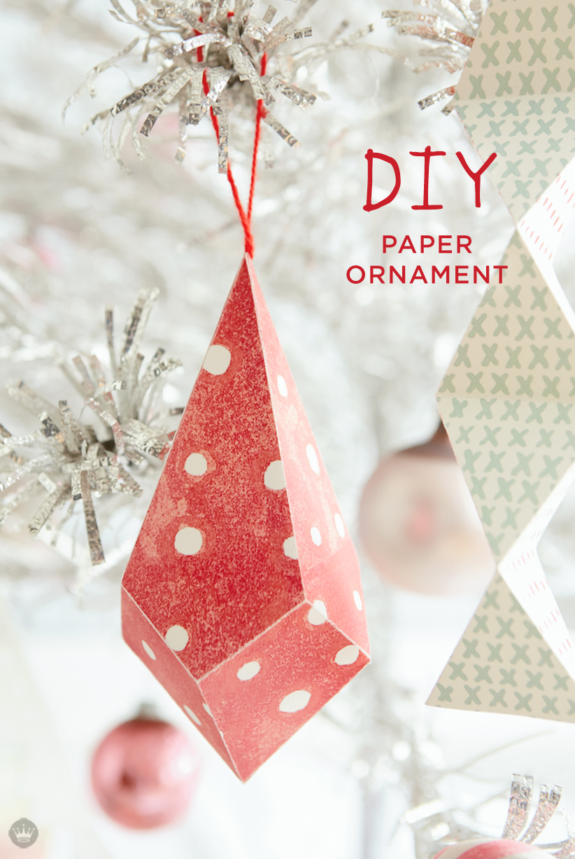 red and white patterned paper ornaments hanging in christmas tree