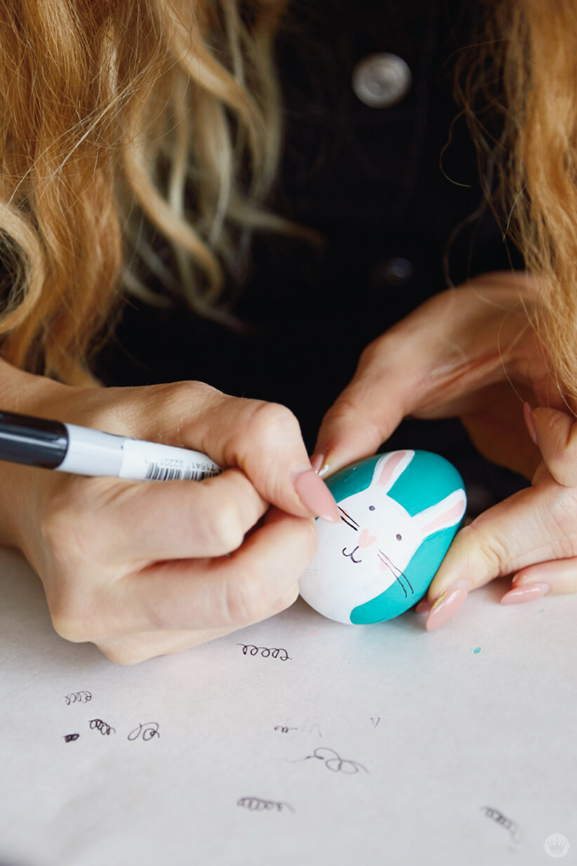 Adding detail to a painted egg with a Sharpie