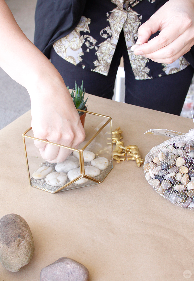 Adding sand and rocks to the bottom of a planter.