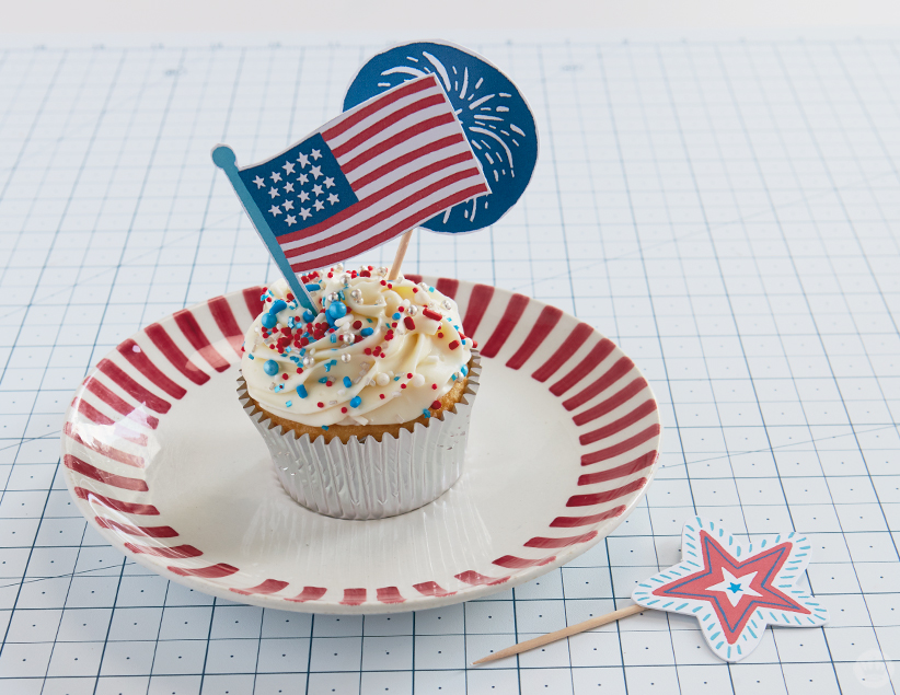 4th of July cupcake decorated with flag and fireworks toppers.