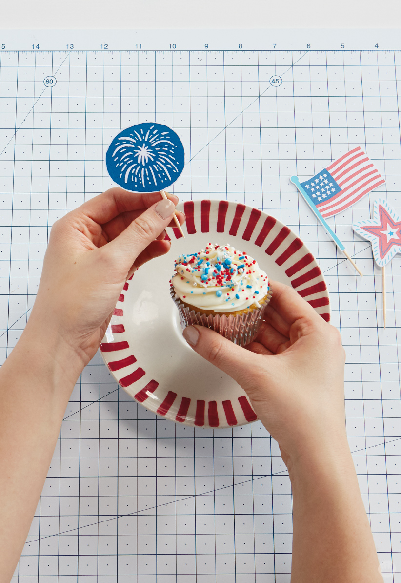 Inserting fireworks topper in frosted cupcake.