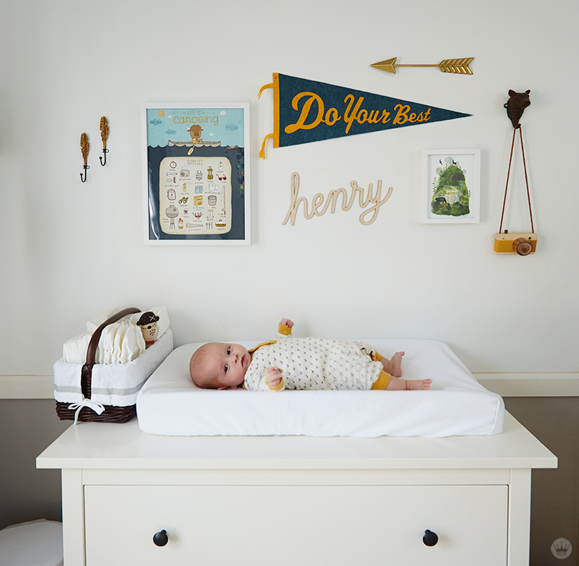 "Tips for displaying art: A gallery wall over a baby on a changing table features a pennant (""Do your best""), the word ""henry"" in rope letters, a print about canoeing, and other pieces of art"