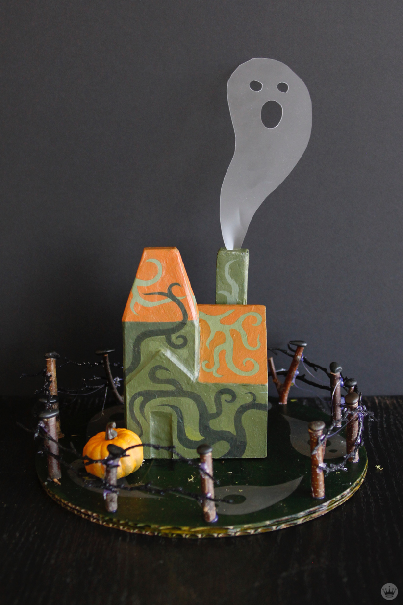 Miniature Haunted House Halloween decorations: Two story green and orange house covered with painted vines; translucent ghost coming out of chimney.