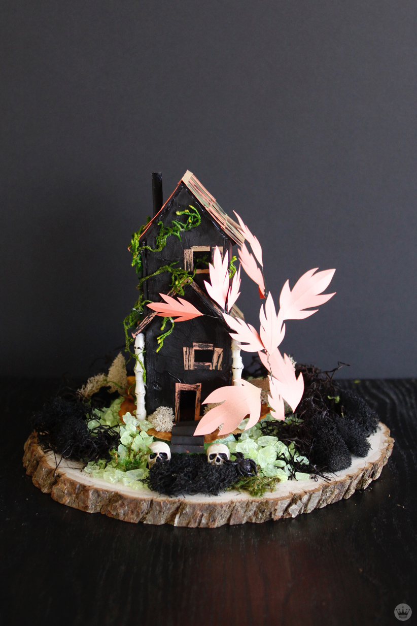 Miniature Haunted House Halloween decorations: Two story clay house, painted black with moss masquerading as ivy and skeletal columns. Also includes paper tree with oversized orange leaves, moss and pebble lawn, and two skulls at the doorway.