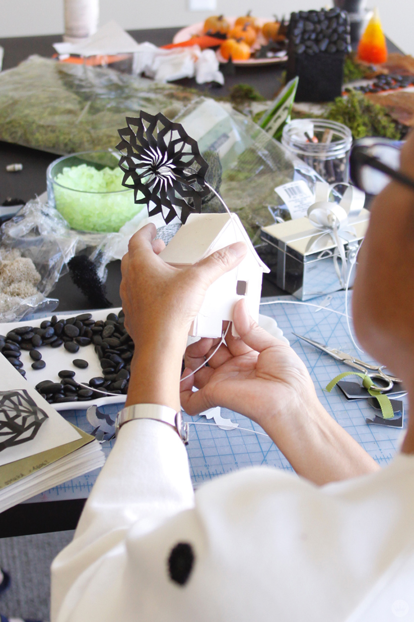 Miniature Haunted House Halloween decorations: Artist adding a black cut paper decoration to a small white clay house.