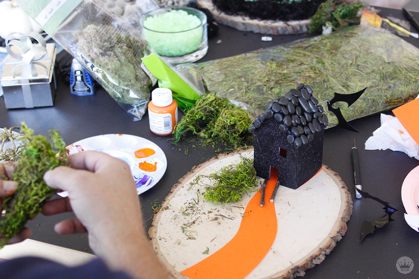 Miniature Haunted House Halloween decorations: Artist adding moss and orange painted road to miniature black house.