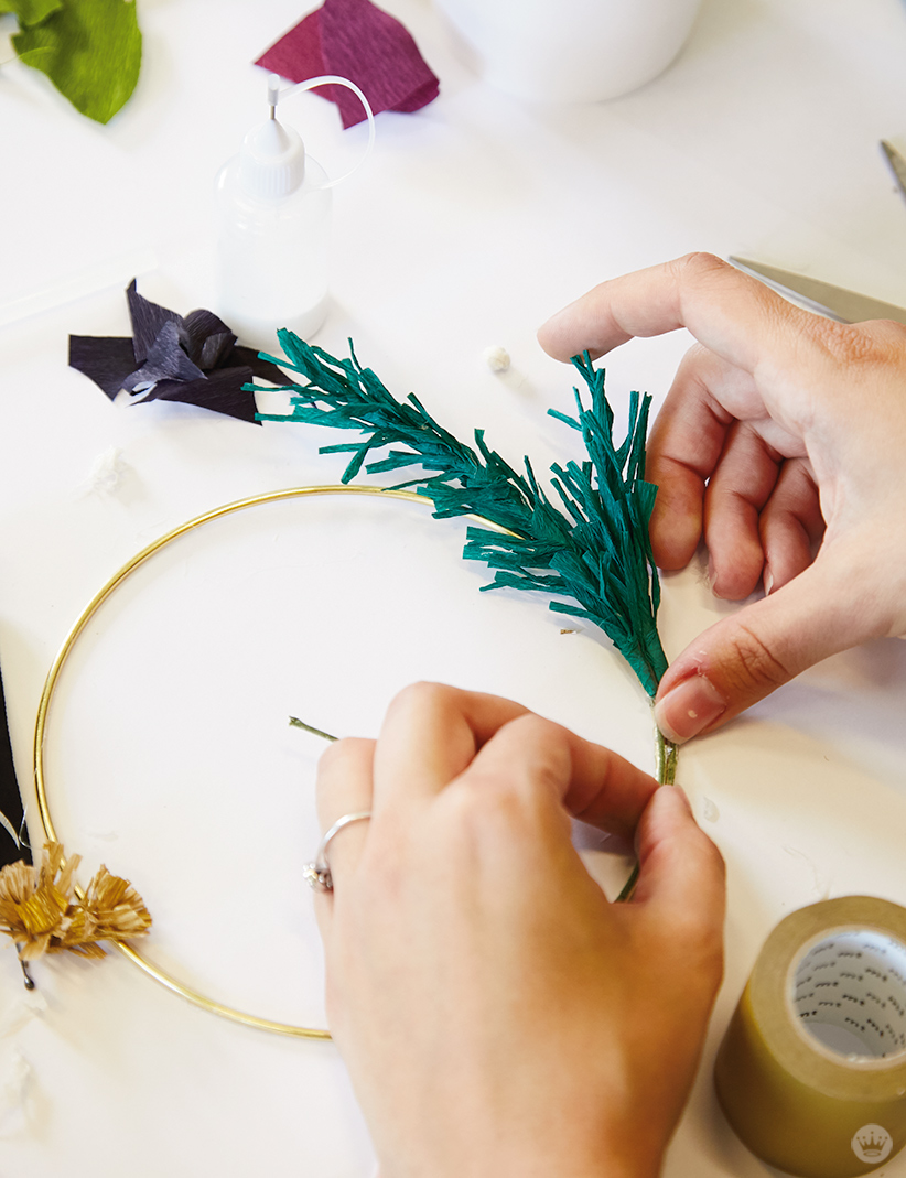 Wrapping teal fringe around a brass ring