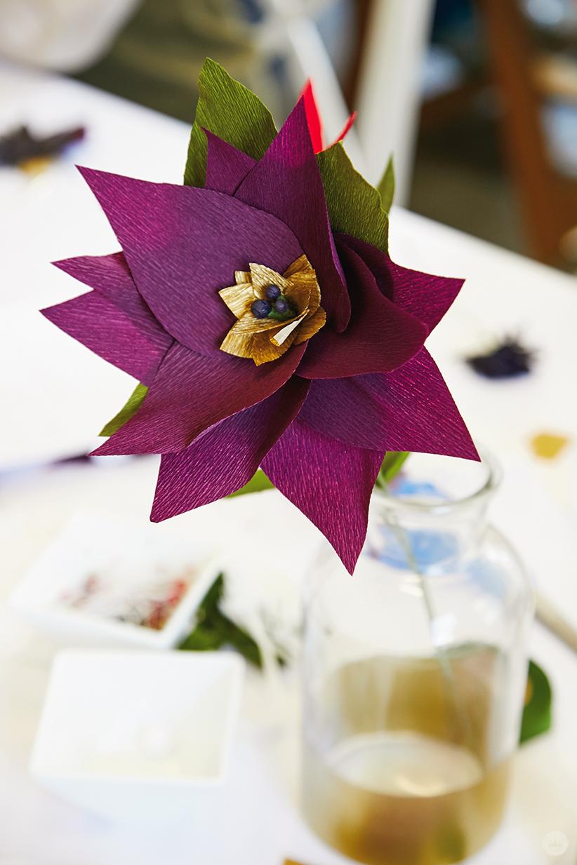 Purple DIY paper poinsettia in a glass vase
