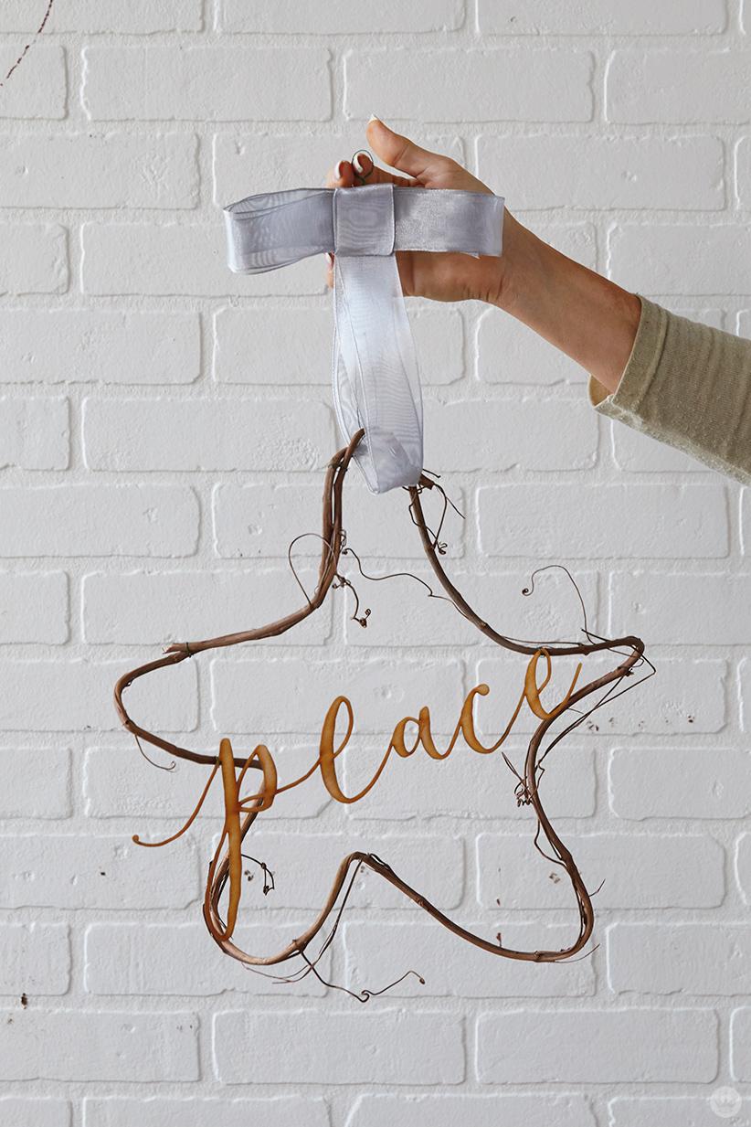 "Modern Christmas wreath ideas: Star-shaped vine wreath with laser-cut ""peace"""
