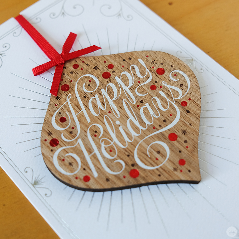 Jessica Hische shows her Signature Style with wooden ornaments attacahed to Christmas cards.