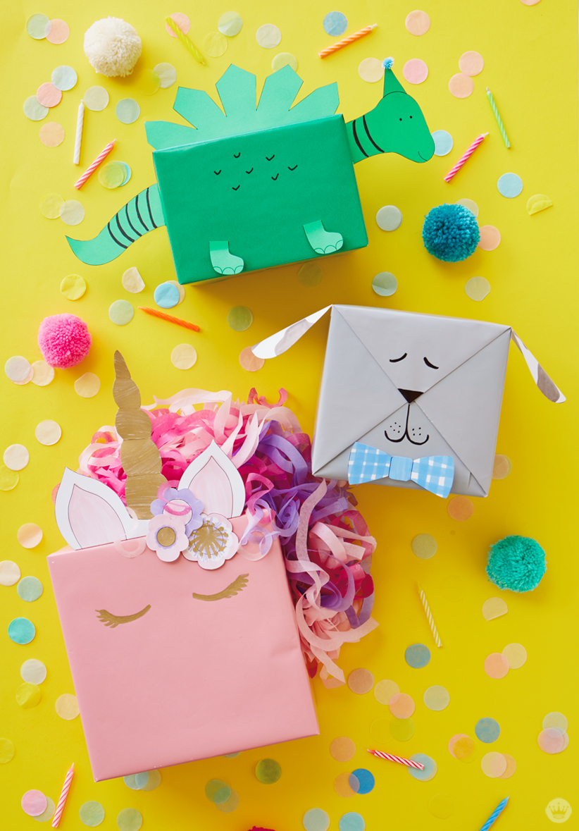 Three kids gift wrap ideas: a green dinosaur, gray dog, and pink unicorn made with free downloadable templates.