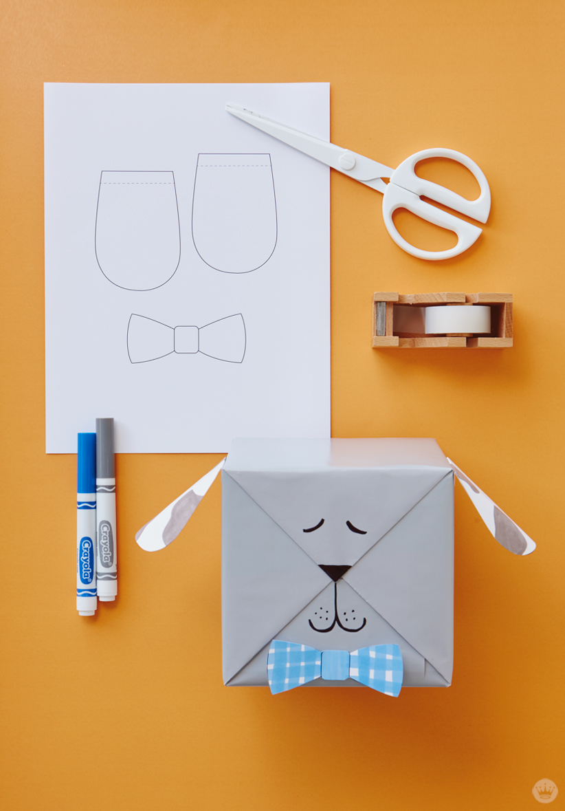 Kids gift wrap idea: dog ears and bowtie printed on white copier paper, tape, scissors, blue and gray markers, and complete wrapped gift.