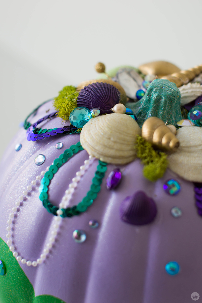 Close-up: Shells, moss, pearls, gems and sequins decorate a lavender and green pumpkin