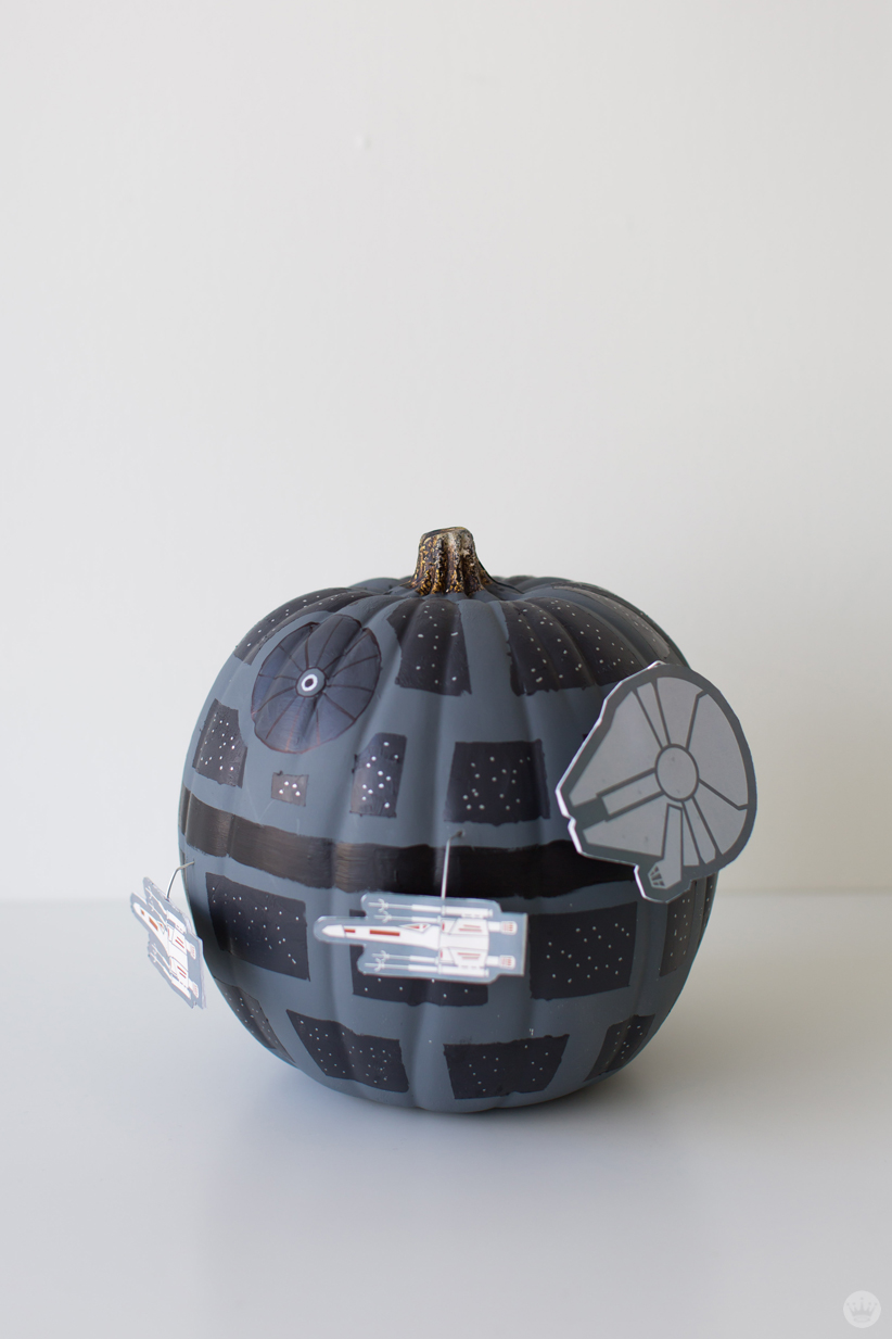 Cut-out drawings of Star Wars ships (X-Wing Fighters, Millennium Falcon) circle a black and gray pumpkin painted to look like the Death Star
