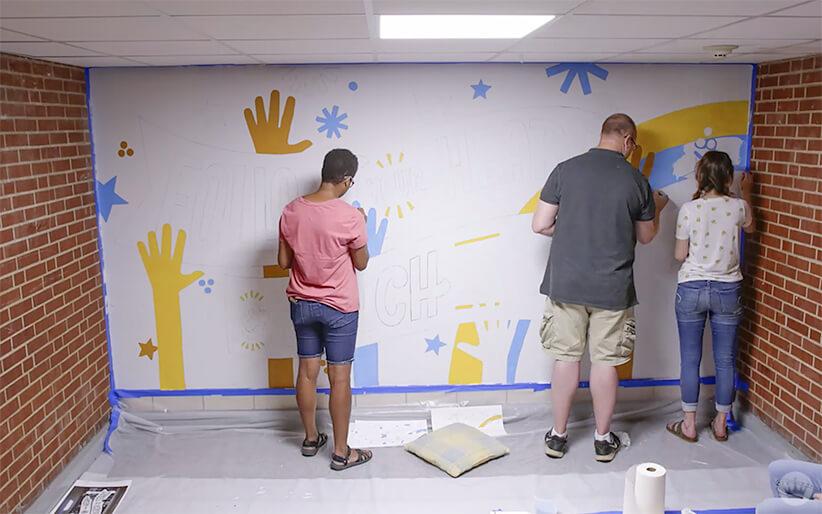 Hallmark artists prepping an inspiring mural at a local elementary school