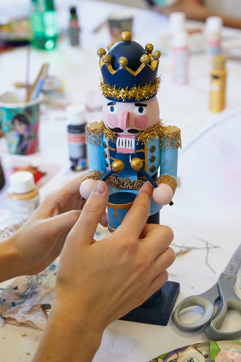 Adding shiny gold trim to a wooden nutcracker's uniform