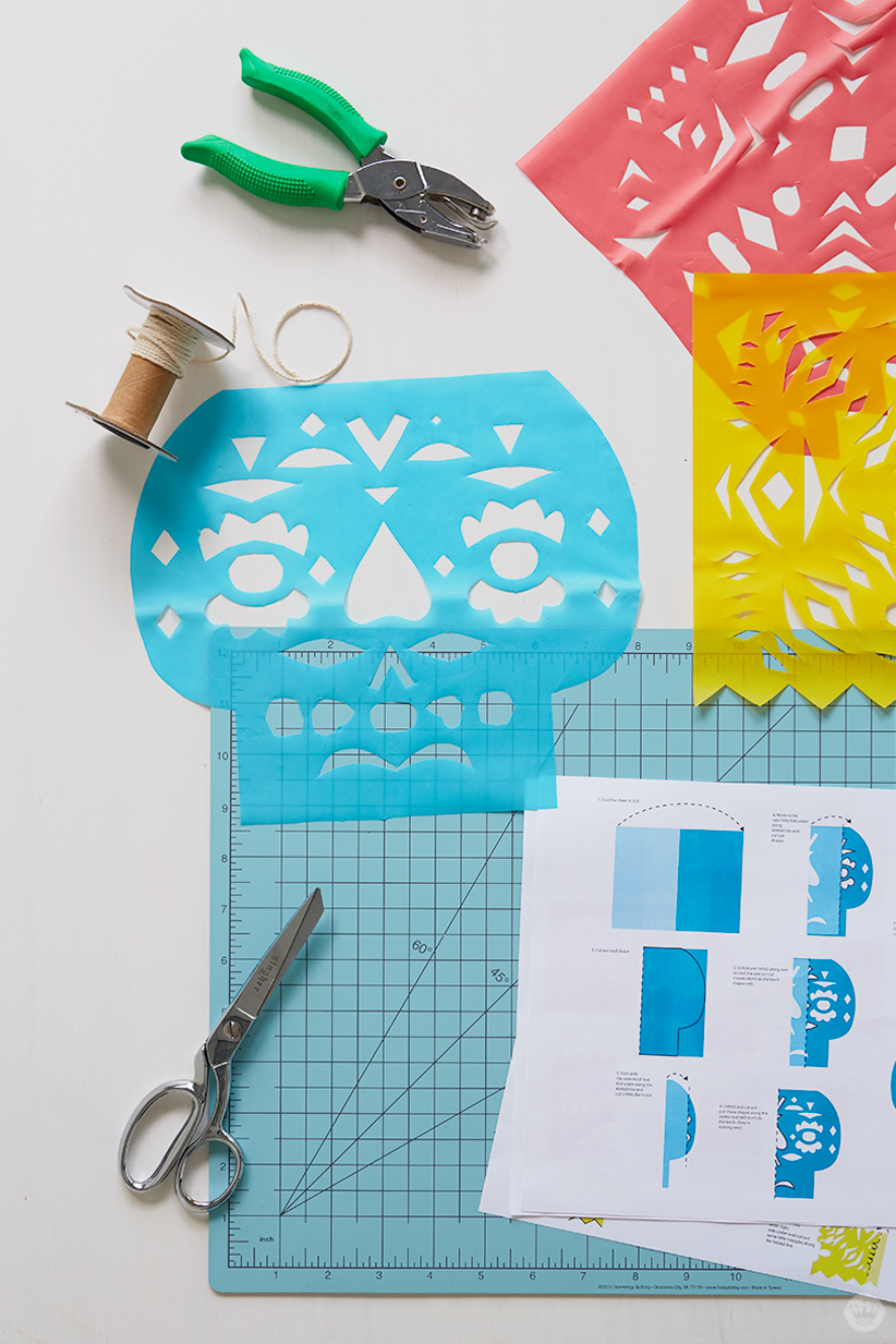Supplies for DIY papel picado: hole punch, string, cutting board, instructions, and three finished banners
