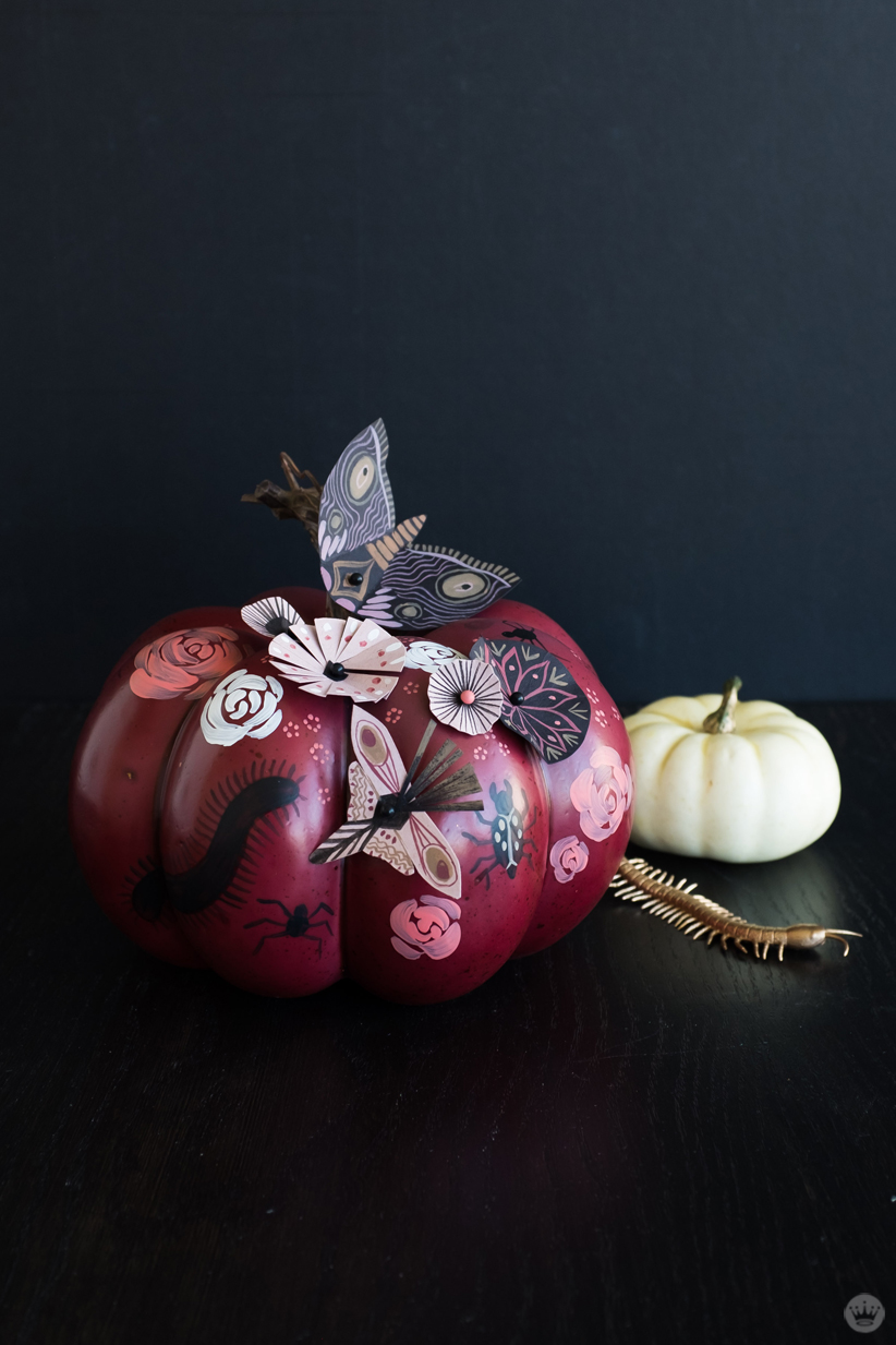 Small reddish pumpkin with painted roses and painted paper attachments—insects and flowers (also shown: small white pumpkin and gold centipede)