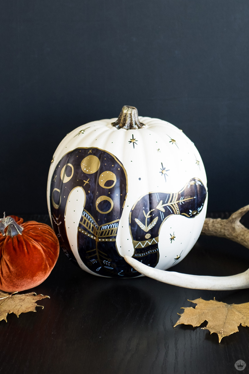 Painted white pumpkin decorated with a black and gold snake