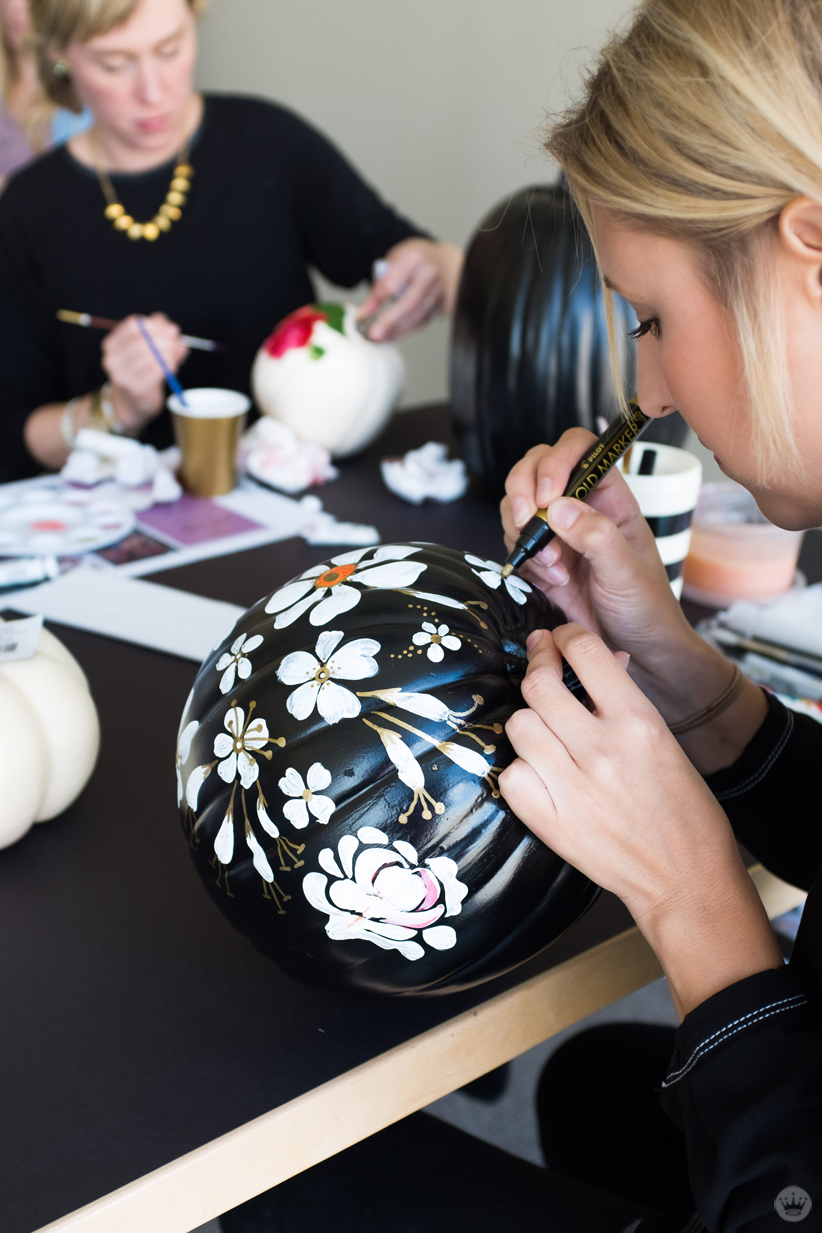 Artist embellishing white painted flowers with gold on a black pumpkin