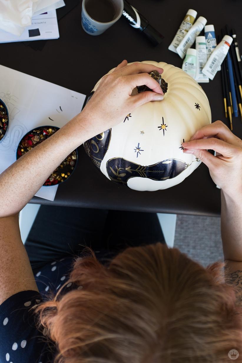 Artist adding gold metallic studs to star-shaped doodles on a white pumpkin