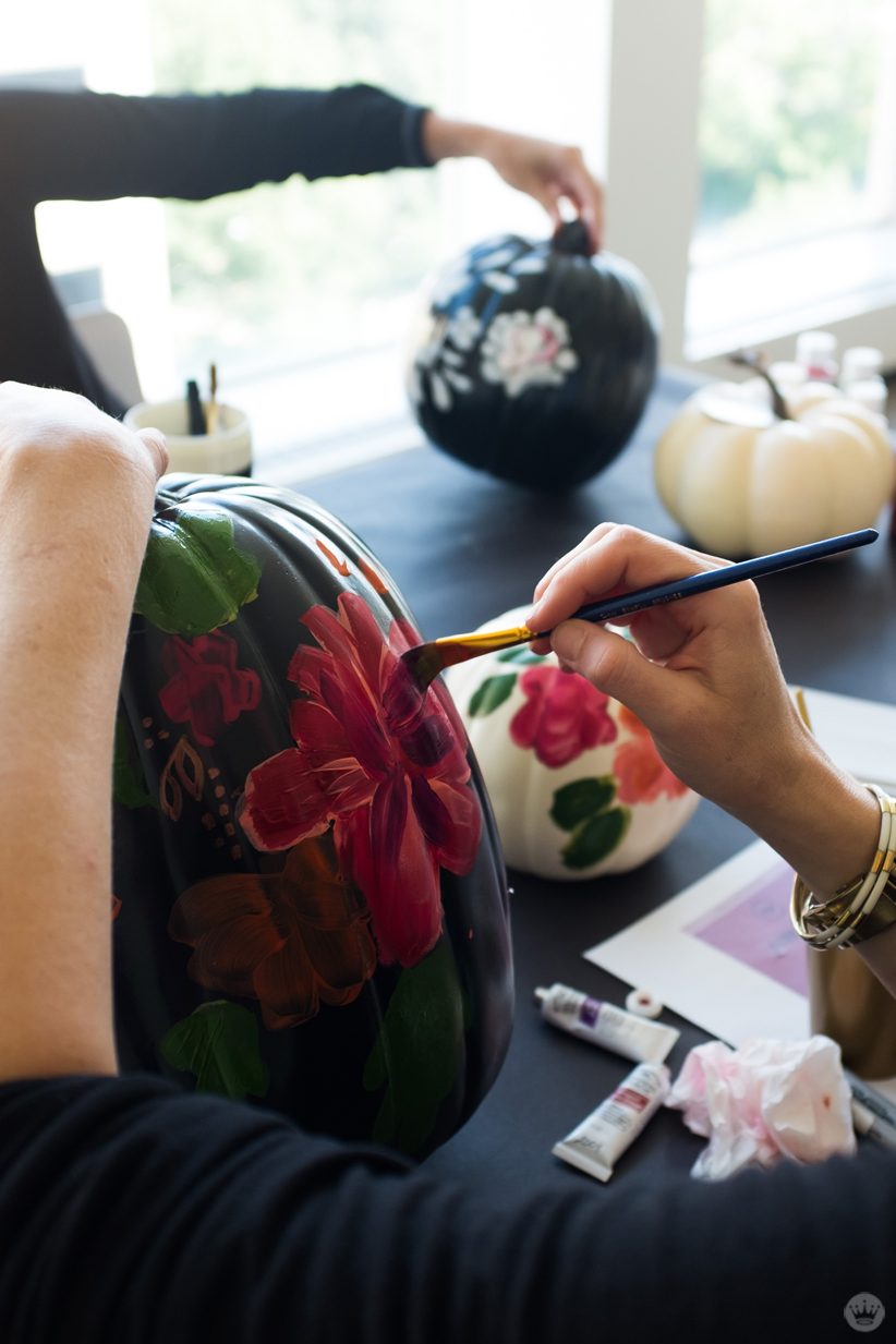 Artist painting large red flowers on a tall black pumpkin
