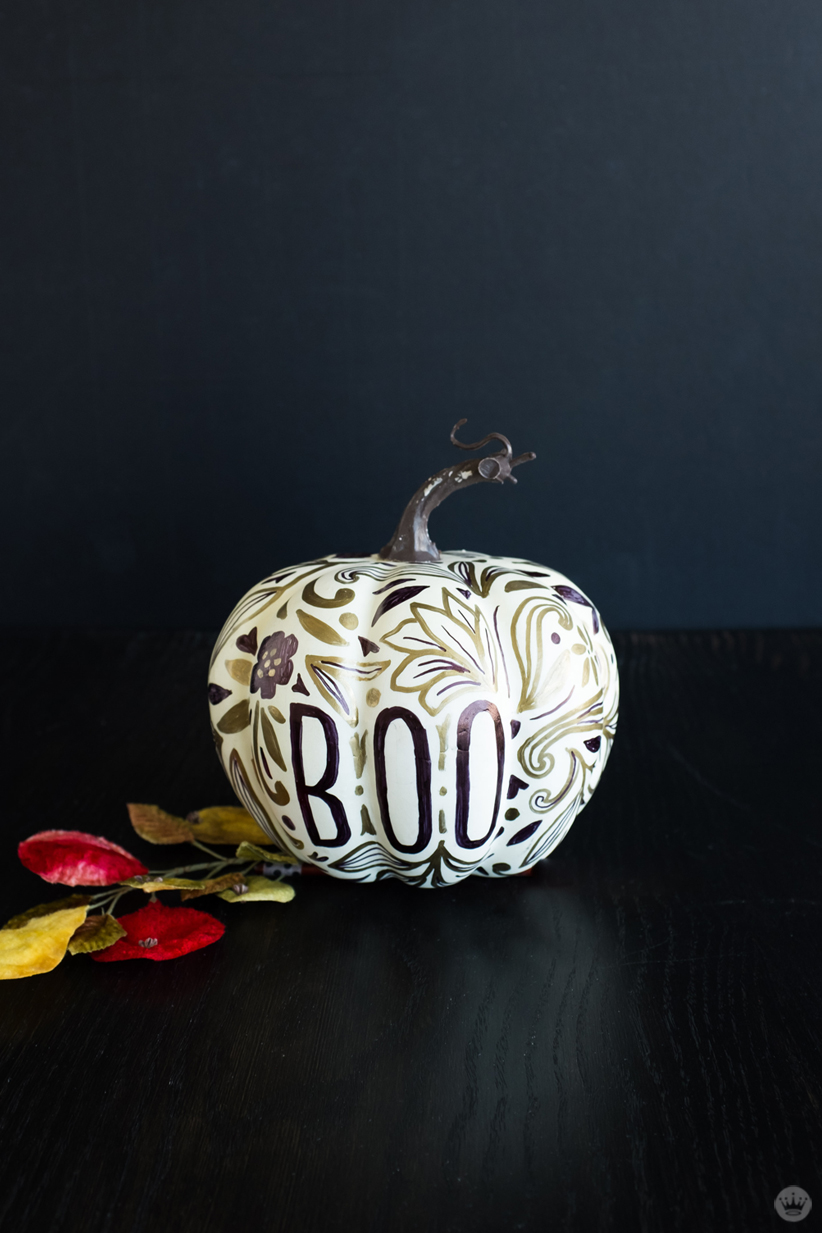 Painted white pumpkin: the word BOO is surrounded by metallic doodles