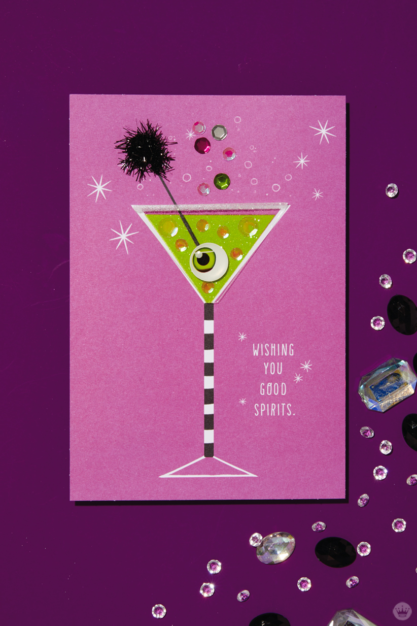 """The Signature card behind our signature Halloween cocktail, the Apple of My Eye-tini: Shimmery fuschia card featuring and black-and-white-stripe-stemmed martini glass filled with green liquid, garnished with an eyeball on a black cocktail pick (includes the message """"WISHING YOU GOOD SPIRITS"""")"""