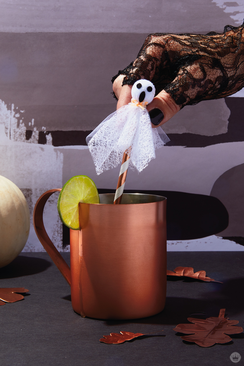 Signature Halloween Cocktails: The Moscow Ghoul (lace-covered ghost attached to a copper and white straw stirring a drink in a frosty copper mug with a lime slice garnish)
