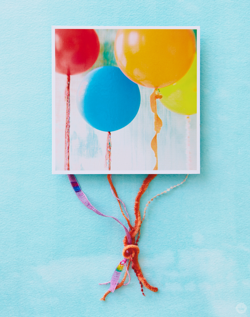 Card featuring photograph of red, blue, orange, green, and yellow balloons