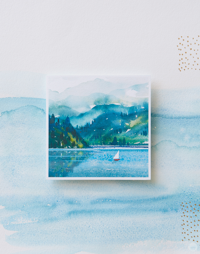 Card featuring a watercolor painting of mountains and a lake with a sailboat