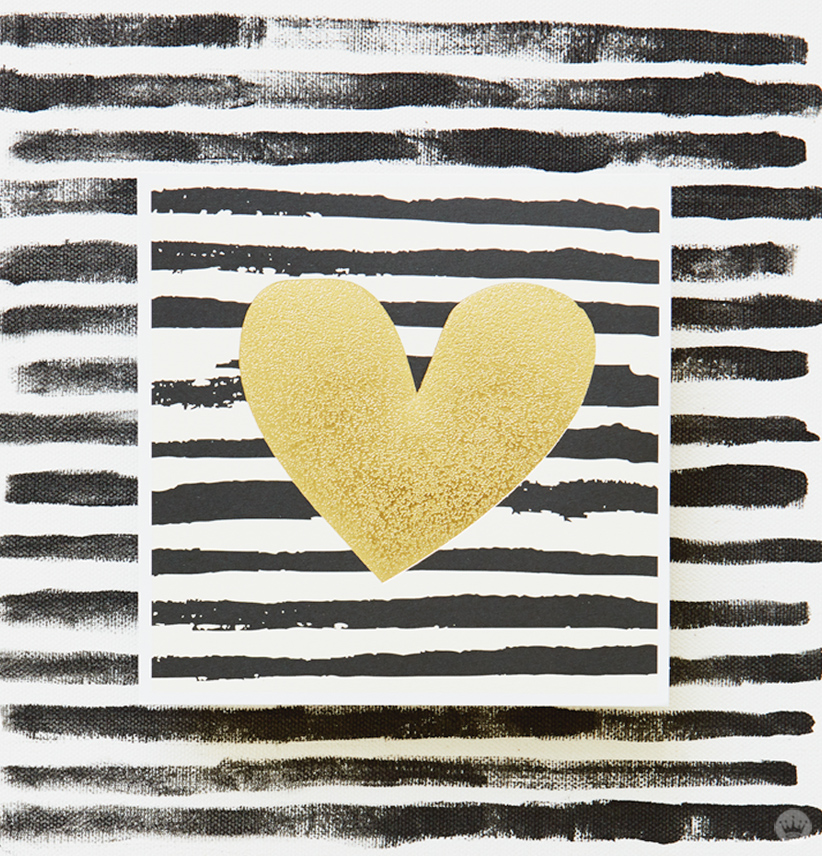 Gold foil heart on a background of black and gray painted stripes