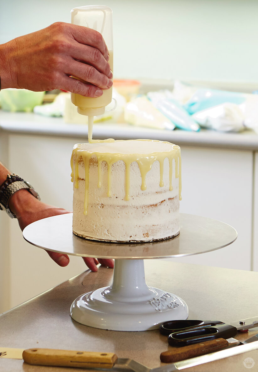 Adding melted white chocolate to a drip cake
