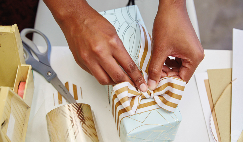Tying a bow on a gift wrapped with Hallmark Classic Luxury wrap.