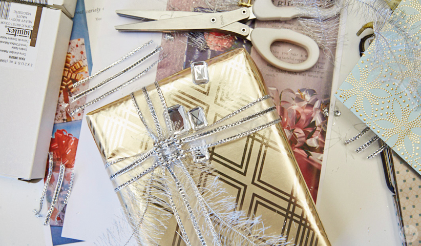 Gold-wrapped wedding gift with sheer ribbon and gems.