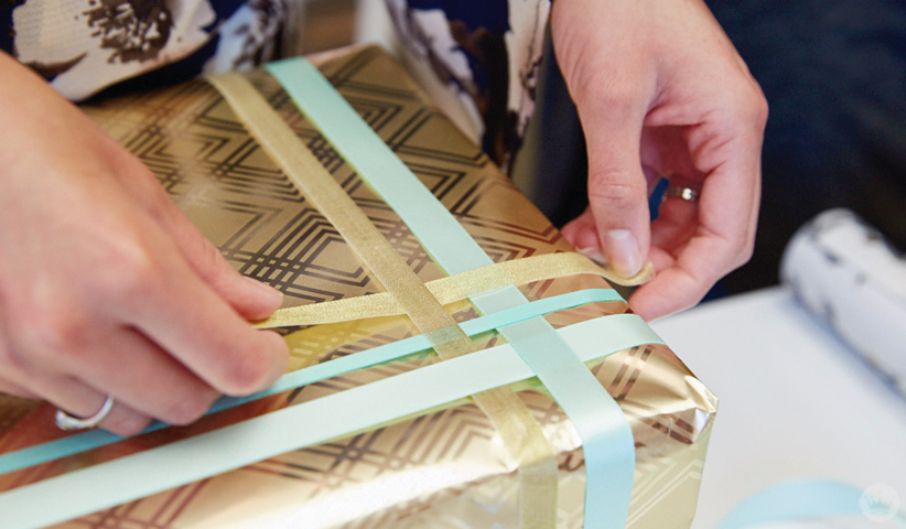 Basketweave wrap with different sizes and colors of ribbon on a wedding gift box.