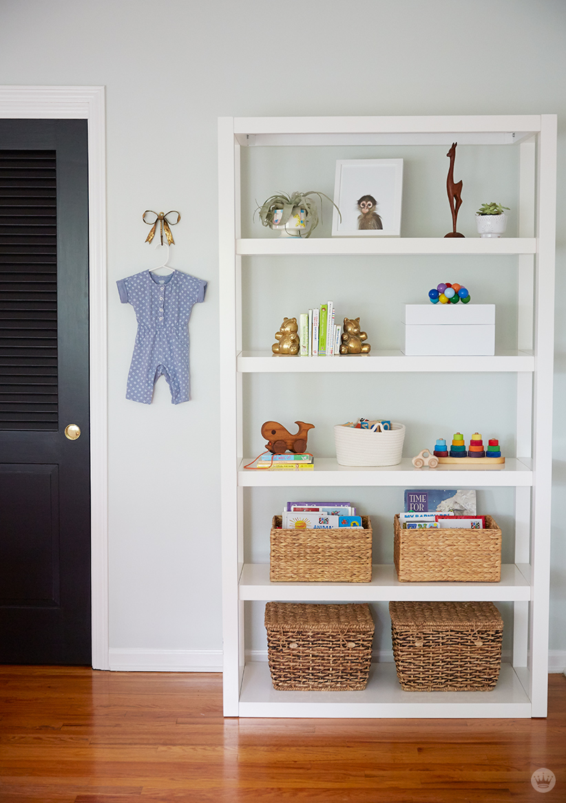 Tips for displaying art: White multilevel shelving filled with framed prints, toys, and baskets; a onesie hangs on the wall